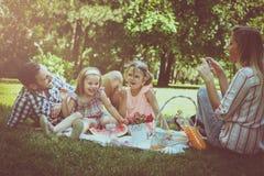 Lycklig familj som tillsammans tycker om i picknick Arkivbild