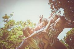 Lycklig familj som tillsammans tycker om i sommardag bärande li för fader Arkivfoto