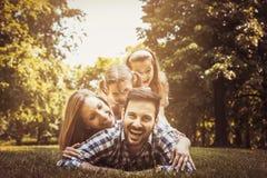 Lycklig familj som tillsammans tycker om i sommardag Ligga för små flickor Royaltyfri Fotografi
