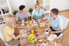 Lycklig familj som tycker om frukosten Arkivfoton