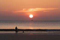 Lycklig familj som tycker om härlig solnedgång på stranden för ferietid, kontursolnedgång på havet Fotografering för Bildbyråer