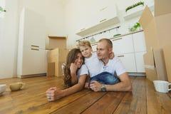 Lycklig familj som tycker om i deras nya tomma lägenhet Royaltyfri Bild