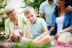 Lycklig familj som tycker om picknicken i natur på sommar royaltyfria foton