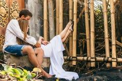 Lycklig familj som tycker om romantisk bröllopsresaferie på den svarta sandstranden Arkivfoton