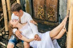 Lycklig familj som tycker om romantisk bröllopsresaferie på den svarta sandstranden Royaltyfri Fotografi