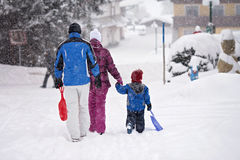 Lycklig familj som ut går vintertid som glider Arkivbilder