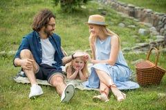 Lycklig familj som utomhus har picknick med deras gulliga dotter, blå kläder, kvinna i hatt royaltyfria foton