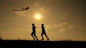 Lycklig familj som utomhus spelar och att flyga drakeflyg Kontur av barn med en drake på solnedgången Lagarbete, laglek arkivfilmer