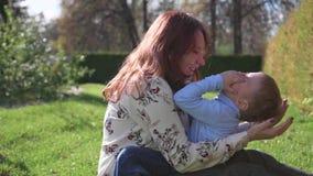Lycklig familj som vilar på gräsmattan Modern med mjukhet och förälskelse spelar med hennes barn, sonskratten, honom har gyckel L arkivfilmer