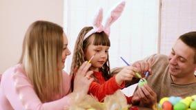 Lycklig familj tillsammans för någon tabellgyckel som förbereder sig för påsken, flicka som rymmer ett ägg, medan henne föräldrar stock video