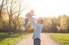 Lycklig familj tillsammans, f?r?ldrar med deras lilla barn p? solnedg?ngen Att lyfta f?r fader behandla som ett barn upp i luften arkivbild