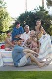 Lycklig familj tillsammans i gräsmatta arkivfoto