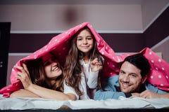 Lycklig familj under en filt Royaltyfri Bild
