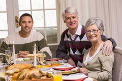Lycklig familj under julmatställe Arkivbild