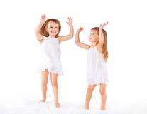 lycklig familj ungar kopplar samman systrar som hoppar på sängen, att spela Royaltyfria Bilder