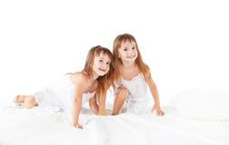 lycklig familj ungar kopplar samman systrar som hoppar på sängen, att spela Arkivbild