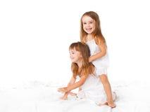 lycklig familj ungar kopplar samman systrar som hoppar på sängen, att spela Royaltyfri Fotografi