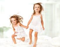 lycklig familj ungar kopplar samman systrar som hoppar på sängen, att spela och att skratta Arkivbild