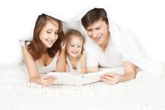 Lycklig familj: uppfostrar avläsningsboken med barnet arkivbild