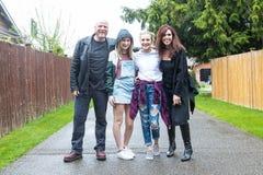 Lycklig familj utanför i regnet royaltyfri bild