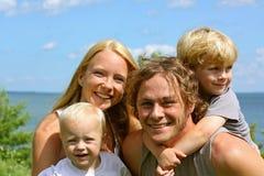 Lycklig familj utanför vid sjön Arkivfoton