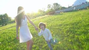 lycklig familj utomhus moder- och sonpys som kör tycka om natursommar på soldagen moder och barn, gullig pojke lager videofilmer
