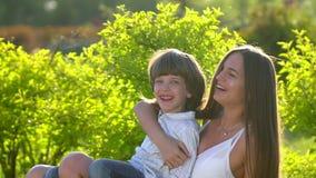 lycklig familj utomhus moder- och sonpys som ler och kramar tycka om natursommar på soldagen Fostra och barnet lager videofilmer