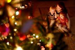 Lycklig familj vid en julgran Arkivbild
