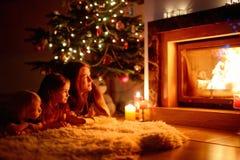 Lycklig familj vid en spis på jul royaltyfria bilder