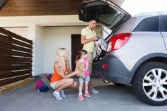 Lycklig familjemballagesaker till hemmastadd parkering för bil Arkivbild