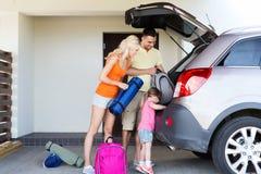 Lycklig familjemballagesaker till hemmastadd parkering för bil Arkivfoto
