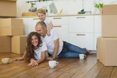 Lycklig familjeplanering deras nya lägenhet boxes den lyckliga pappfamiljen fotografering för bildbyråer