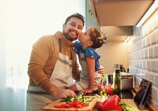 Lycklig familjfader med barndottern som förbereder grönsaksallad arkivfoto