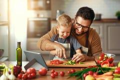 Lycklig familjfader med sonen som f?rbereder gr?nsaksallad royaltyfria bilder