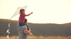 Lycklig familjfader och barn på äng med en drake i sommar Arkivfoto