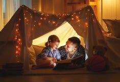 Lycklig familjfader och barndotter som läser en bok i tält arkivbild