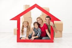 Lycklig familjflyttning in i ett nytt hem royaltyfri bild