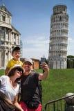 Lycklig familjhandelsresande som framme tar selfie och har roligt av det berömda lutande tornet i Pisa & x28; Unesco& x29; royaltyfria foton