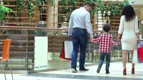 Lycklig familjjul som shoppar i galleria Pojken rymmer en hand modern och fadern Föräldrar och barn med packar arkivfilmer