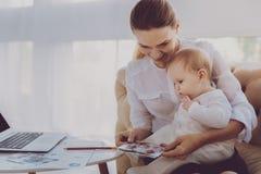 Lycklig familjkvinna som visar foto till hennes småbarn som sitter i vardagsrum royaltyfria bilder