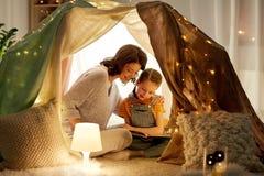 Lycklig familjläsebok i ungetält hemma fotografering för bildbyråer