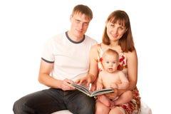 Lycklig familjläsning en boka och le. Arkivfoton