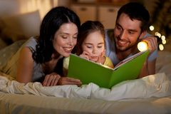 Lycklig familjl?sebok i s?ng p? natten hemma arkivfoto