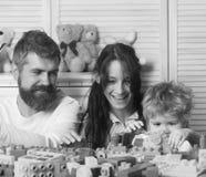 Lycklig familjlek Familj som spelar med färgrika plast- kvarter Föräldrar och unge Arkivbild
