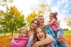 Lycklig familjlek i höst parkerar små ungar för kram Arkivbild