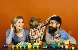 Lycklig familjlek Mannen med skägget, kvinnan och pojken spelar på röd bakgrund Arkivfoto