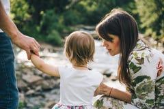 Lycklig familjlek med dottern nära floden i berg Fotografering för Bildbyråer