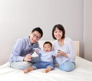 Lycklig familjlek på säng Royaltyfria Bilder