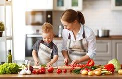 Lycklig familjmoder med barnsonen som förbereder grönsaksallad royaltyfri fotografi