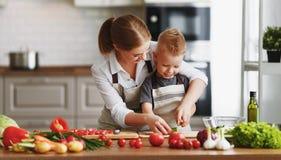 Lycklig familjmoder med barnsonen som förbereder grönsaksallad royaltyfria bilder